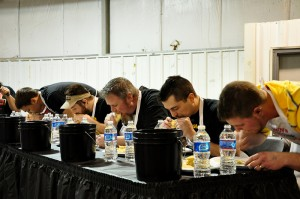 Buckets and bottles of water line the table at the annual pierogi-eating challenge as participants compete to eat as many pierogies as possible in three minutes. The event was part of the Seventh annual Men's culinary Classic, held March 10th at the Washington Co. Fairgrounds to benefit Community Action Southwest. Photo by Justine Coyne.
