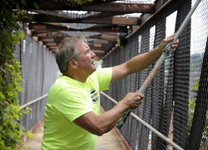 Jeff Neubauer, 64, of the South Side use a paint roller to reach graffiti on the 15th Street Bridge.  Photo by Evan Skowvron | Point Park News Service