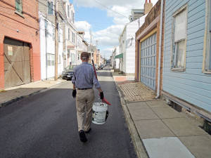 Volunteer Adam Christian walks down his South Side street to start his trash-collecting route. Photo: Joel Anderson | Point Park News Service