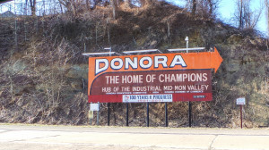"""People traveling into Donora from the Monessen Bridge are greeted with a large billboard proclaiming Donora as the """"Home Of Champions"""" and the """"Hub of the Industrial Mid Mon Valley."""" Holly Tonini / Point Park News Service"""