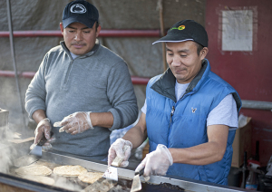 Alejandro Cortez and Nicolas Rimirez work at the taco stand outside of Las Palmas on Broadway Avenue in Beechview. Photo: Sarah Collins | Point Park News Service