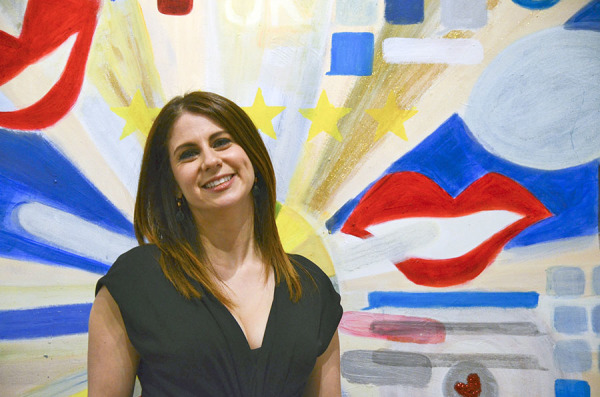 Artist Andi Irwin stands in front of her paintings in her art show 'Kiss My Apps' at BE Galleries in Lawrenceville.<br /> Photo: Haley Wisniewski | Point Park News Service