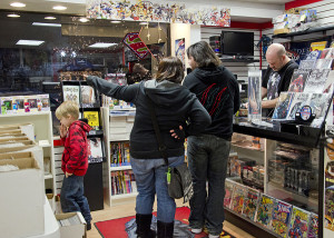 Matthew Standiford waits to check out his purchases at Big Bang Collectibles and Comics in Sewickley with his wife, Desiray, and son, Caden.<br /> Photo: Haley Wisniewski | Point Park News Service