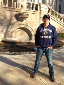 Alex Austin poses in front of the fountain at the University of Pittsburgh where students met for the Million Student March. Photo by Alicia Green.